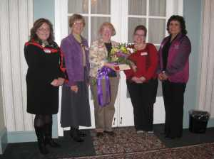 Daphne Dumont, centre, receives flowers from women's organizations. Left to right: Lisa Murphy, representing LEAF PEI; Isabelle Christian, Chairperson of the PEI Advisory Council on the Status of Women; and Lorraine Phaneuf and Dollie Simon from the Status of Women Council of the Northwest Territories, representing the Coalition of Advisory Councils.